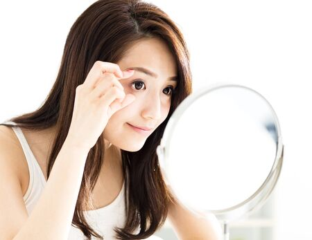 woman mirror: young woman looking into mirror and checking eyes