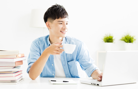 relaxed young man studying and drinking coffee
