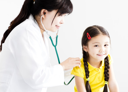 Female Doctor examining  little girl by stethoscope photo