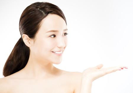 Young woman showing  beauty product on hand