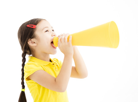 Happy little girl shouting by megaphone Standard-Bild