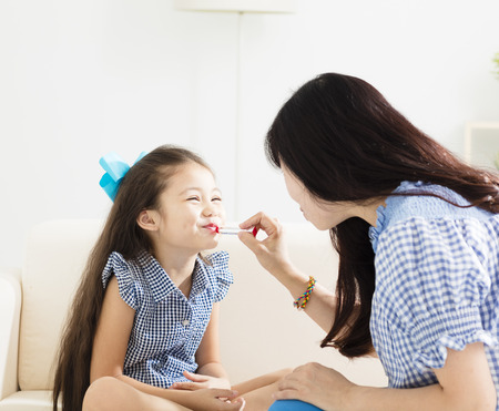 Little girl playing makeup with mothers photo