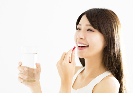 cup: smiling young woman eating the pill