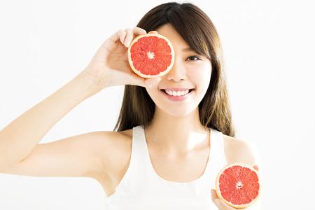 Gelukkige Vrouw die haar oog met grapefruit bedekt Stockfoto