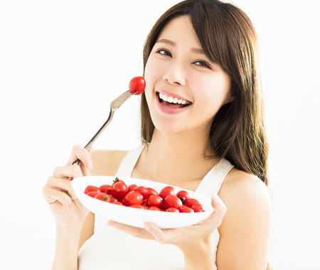 beautiful Young Woman Eating Tomatoes
