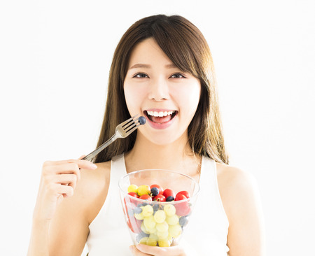 Happy young woman eating fresh fruits