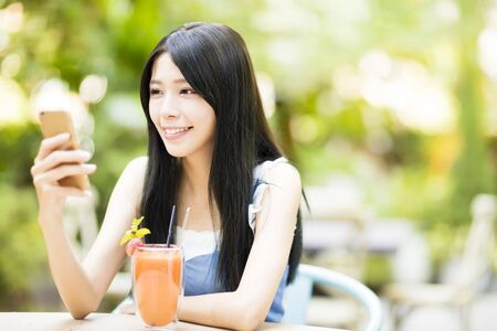 smiling young woman sitting in restaurant watching smart phone