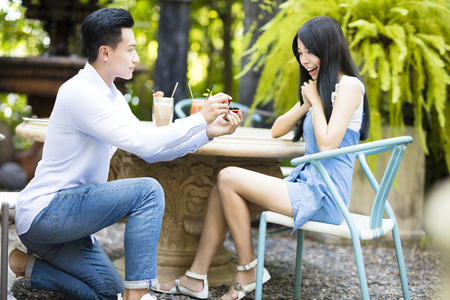 Man proposing to girlfriend offering engagement ring in restaurant Stock Photo