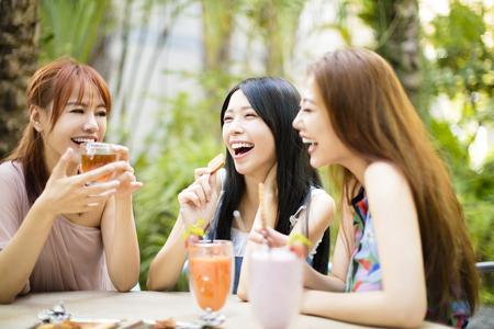 庭にレストランを話して女性の友人のグループ 写真素材