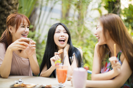 Happy young woman talking In Restaurant garden Stock Photo