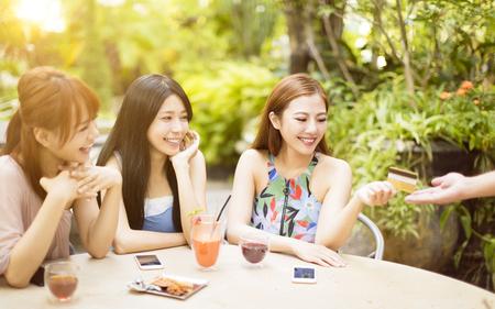 젊은 여자가 신용 카드로 레스토랑에서 청구서를 지불