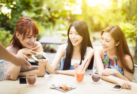 Giovane donna pagando conto con smart phone in ristorante Archivio Fotografico - 86439269