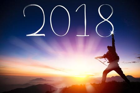 행복 한 새 해 개념입니다. 2018을 산 꼭대기에 손전등으로 그리는 남자