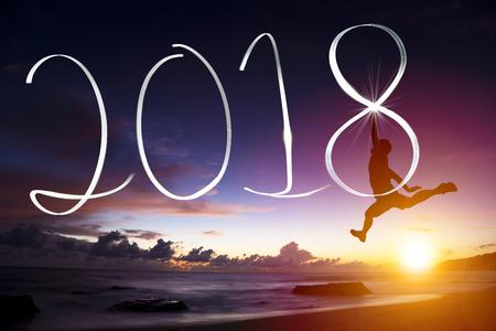 Happy new year concept.young uomo che salta e disegna il 2018 Archivio Fotografico - 87602310