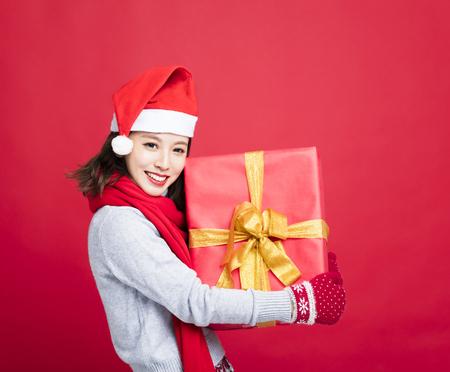 Glückliche Frau, welche die Weihnachtsgeschenkbox zeigt Standard-Bild - 88279141