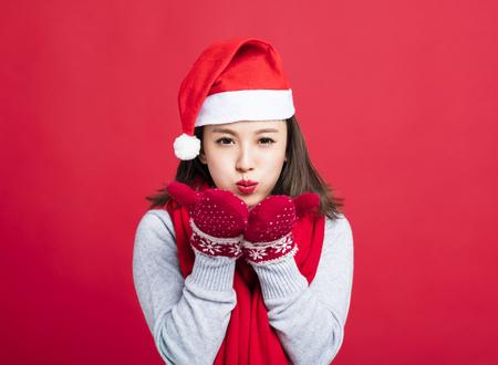 joven mujer de Navidad soplando la nieve