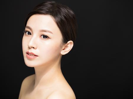 黒の背景に分離されたクローズ アップ美容女性顔