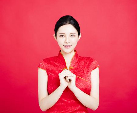 中国の cheongsam でのアジアの女性のお祝いのジェスチャーで