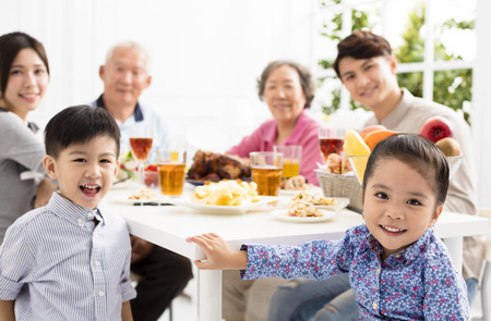 Felice famiglia asiatica a cena a casa Archivio Fotografico - 89509935