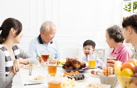 gelukkige Aziatische familie die diner heeft thuis