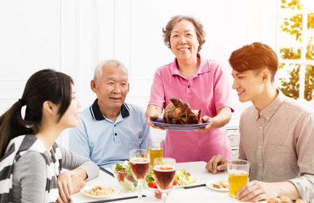 Happy family having dinner together Stock Photo - 89770502