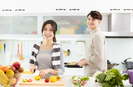 happy young Couple cooking in the kitchen Archivio Fotografico