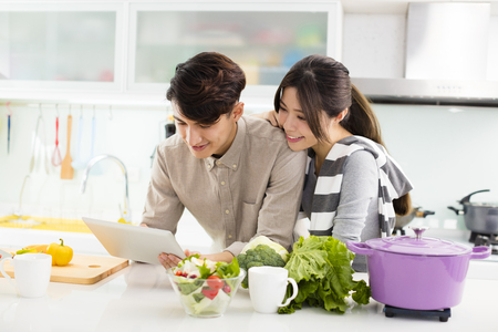 young asian couple cooking in kitchen