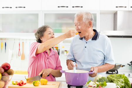 happy senior couple cooking in kitchen Stockfoto