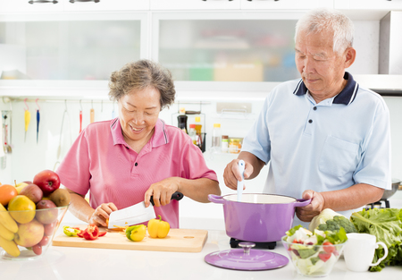 happy senior couple cooking in kitchen Imagens