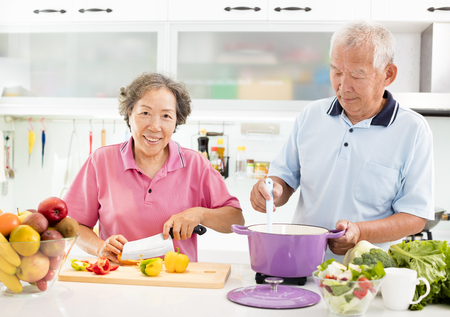 happy senior couple cooking in kitchen Stock Photo