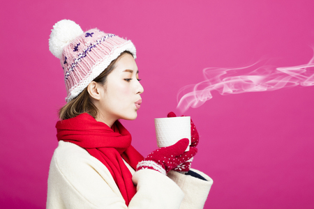 woman in warm sweater drinking a cup of hot tea