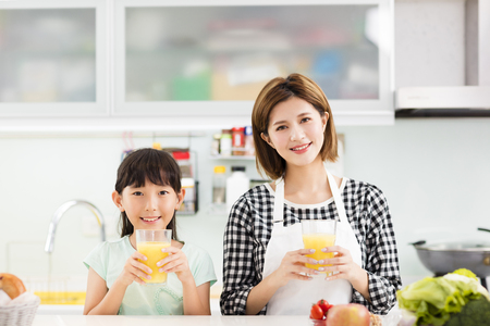 Happy mother and child in kitchen drinking juice Stockfoto