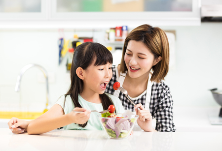 Happy mother and child in kitchen eating salad