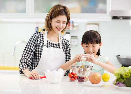 Happy mother and child in kitchen preparing cookies  Stok Fotoğraf