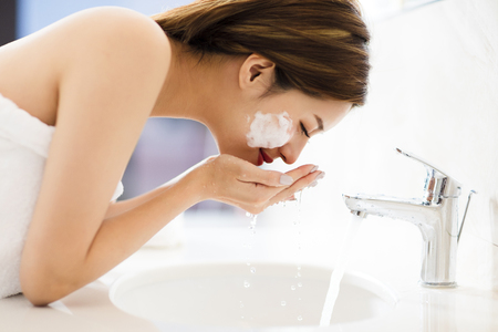 Young woman washing face with clean water in bathroom