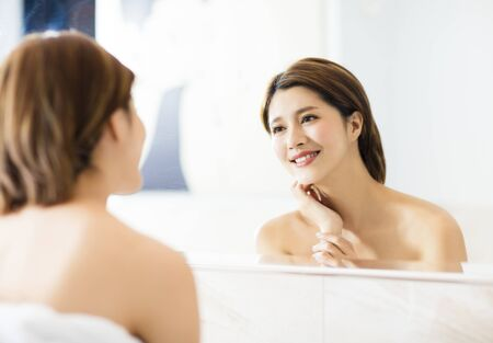 young woman looking on reflection in the mirror at bathroom