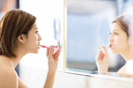 young woman brushing teeth and looking in the mirror  Stock Photo
