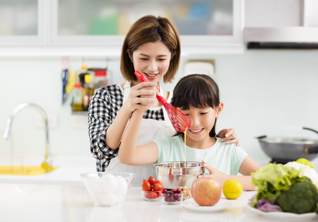 Happy mother and child in kitchen preparing cookies  Imagens
