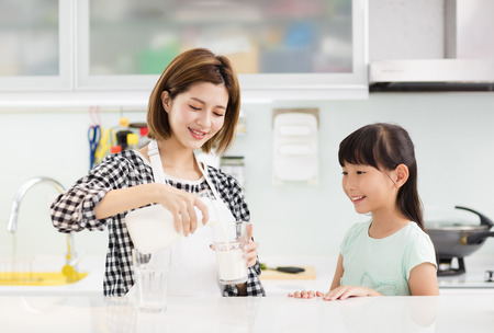 Happy mother and child in kitchen drinking milk