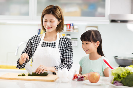 Happy mother and daughter cooking in the kitchen