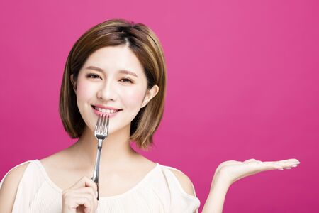 young woman holding fork and showing tasty food   Stock Photo