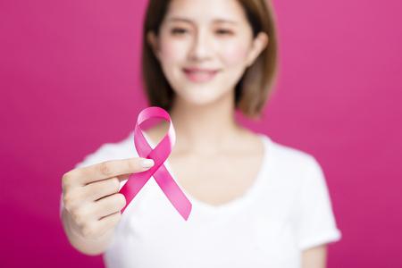 Mão de mulher mostrando a fita de conscientização de câncer de mama rosa