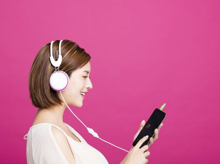 woman listening music with headphones and smart phone