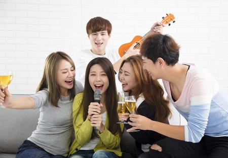 마이크를 잡고 노래방에서 노래하는 젊은 여자 스톡 콘텐츠 - 91442713