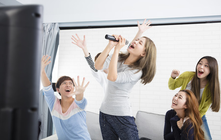 young woman holding microphone and singing at karaoke