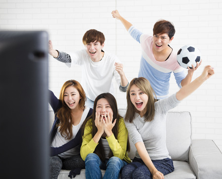 young group Watching Sports On Television And Cheering