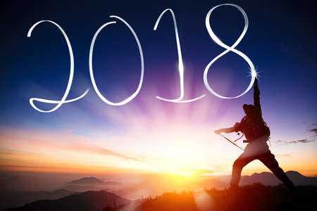 happy new year concept. man drawing 2018 on the mountain