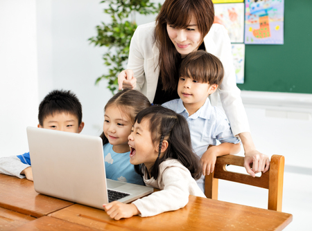 children looking at the laptop with teacher near by