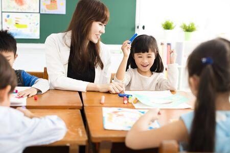 Glückliche Kinder zeichnen im Klassenzimmer und Lehrer in der Nähe
