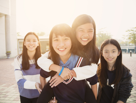 Group Of Teenage Students playing in school